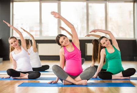 clase media: Grupo de mujeres jóvenes embarazadas están haciendo ejercicio de relajación en la estera de ejercicio