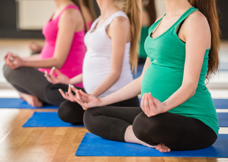 Three pregnant women is doing exercise at gym.