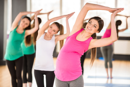 pregnant exercise: Beautiful pregnant women in yoga class standing in a fitness studio, doing exercise.