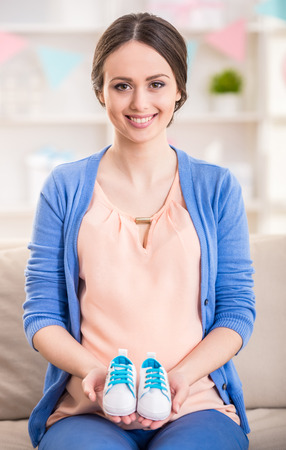 unborn: Beautiful pregnant woman is holding small shoes for the unborn baby. Stock Photo