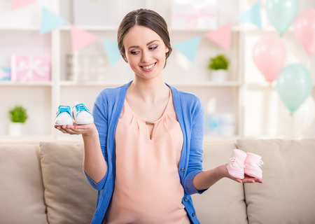 baby boy: Pregnant woman is holding small shoes for the unborn baby. Boy or girl? Stock Photo