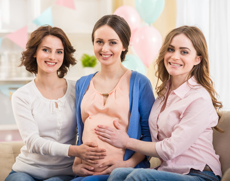 Beautiful pregnant woman with her friends smiling at camera. photo