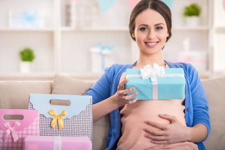 bebe sentado: Mujer embarazada feliz est� sentado con los presentes en un baby shower. Foto de archivo