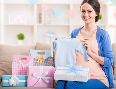 Happy pregnant woman is sitting with presents at a baby shower. photo