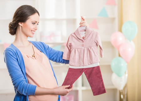 Beautiful pregnant woman is looking at the baby clothes. Stock Photo