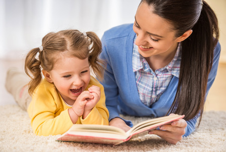book: Young mother is reading a book to her cute daughter. Stock Photo