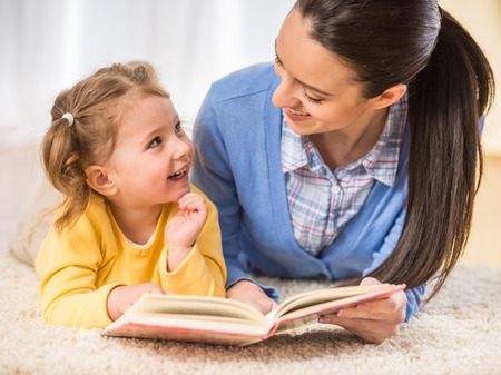 reading: Young mother is reading a book to her cute daughter. Stock Photo