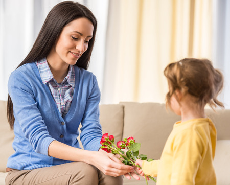 Little girl is giving bouquet of red rose to her mom photo