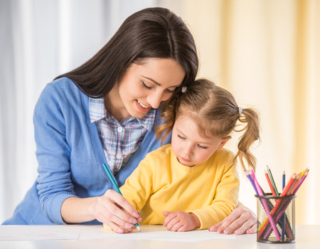 Mother and daughter are having fun while drawing at home.