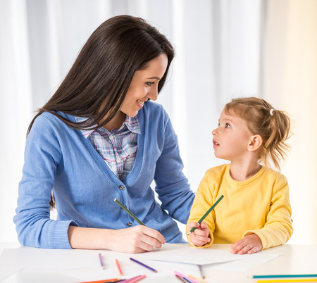 teaching adult: Mother and daughter are having fun while drawing at home.