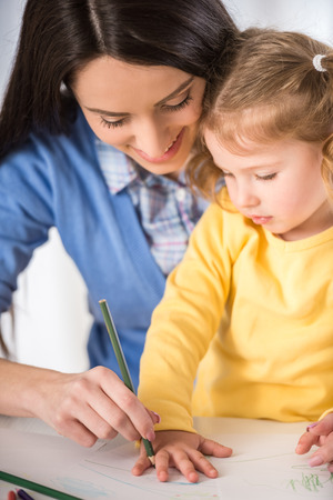 girl drawing: Mother and daughter are having fun while drawing at home.