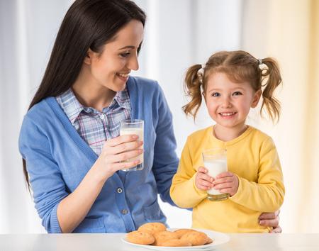 leche: Adorable niña está teniendo un bocado sano con las galletas y la leche con su madre.