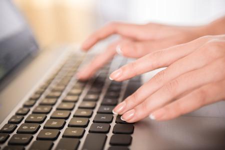 オフィスのノート パソコンのキーボードで入力する手のクローズ アップ。