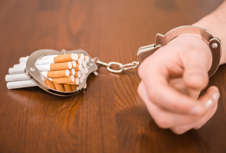 Man hand with handcuffs and cigarettes on the table. The concept of smoking dependence. Stock Photo