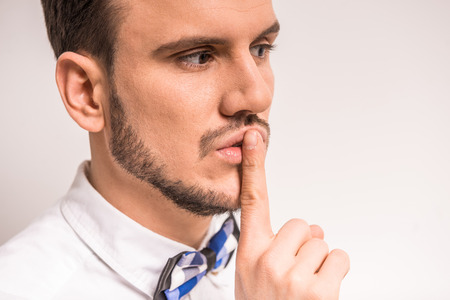 Keep silence! Handsome young man in white shirt is holding finger on lips while standing against grey background.