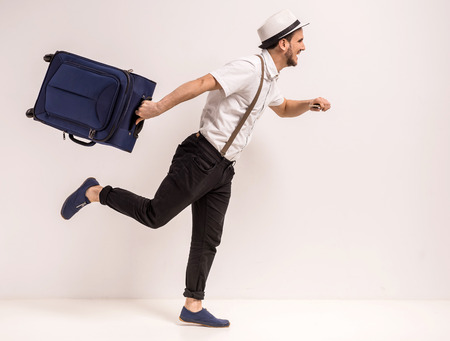 Young creative man is posing with suitcase on grey background. Stock Photo - 39458305