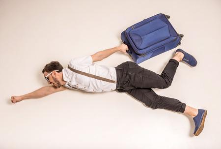 Jonge creatieve man is poseren met een koffer op een grijze achtergrond.