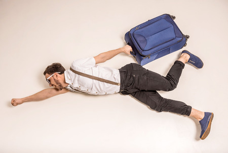 side views: Young creative man is posing with suitcase on grey background.
