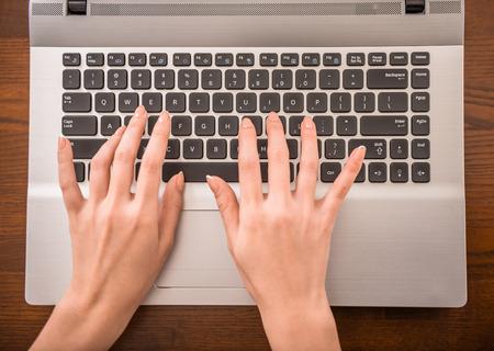 teclado: Vista superior de las manos escribiendo en el teclado del ordenador portátil en la oficina.