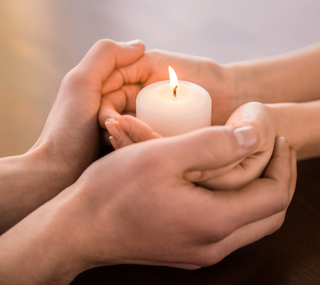 boy and girl holding hands: Young couple are holding hands and candle on the table.