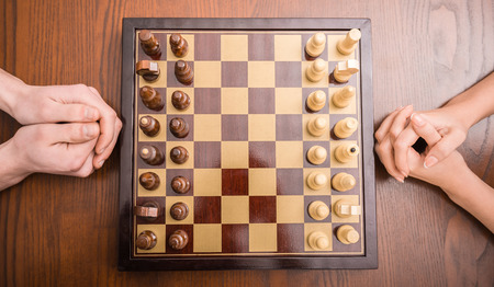 Top view of two people are playing chess. Close-up of chessboard and hands. photo