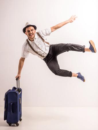 Il giovane creativo sta proponendo con la valigia su sfondo grigio. Archivio Fotografico - 39458355