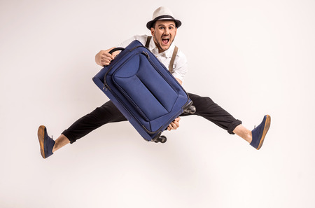 Young creative man is posing with suitcase on grey background. 版權商用圖片 - 39458357