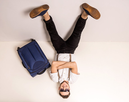 Young creative man is posing with suitcase on grey background. photo