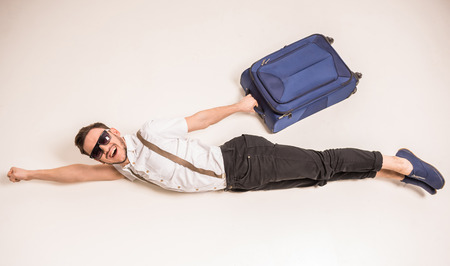 Young creative man is posing with suitcase on grey background.
