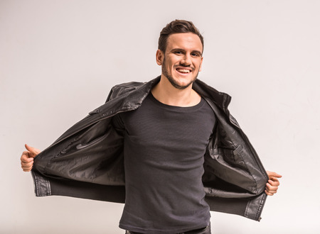 chaqueta de cuero: Hombre joven en la chaqueta de cuero que mira la cámara y sonriendo.