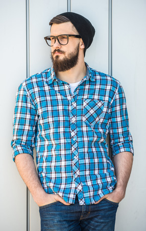 Young bearded man in hat  and glasses is standing outdoor and looking away. photo