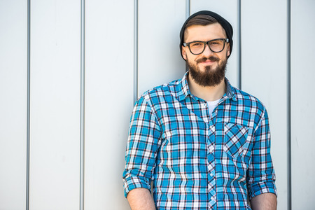 Young smiling man with beard in glasses and hat is looking at the camera. Outdoor. photo
