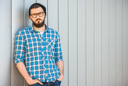 Young confident man with beard in glasses and hat is looking at the camera. Outdoor. photo