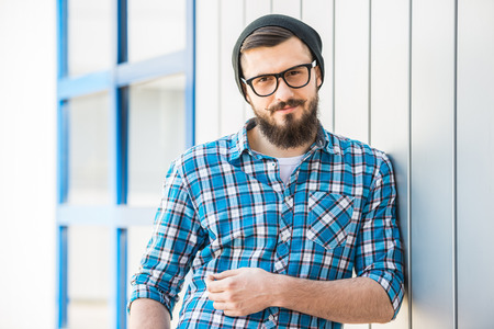 Portrait of young bearded man in hat and glasses outdoor. photo