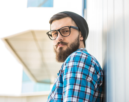 Young trendy man is standing outdoor in hat and glasses and looking at the camera. photo