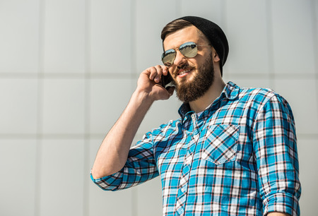 Young bearded man is talking by phone. Outdoor. photo