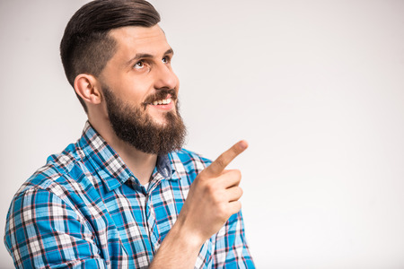Side view of  young smiling man with beard is pointing on something. photo