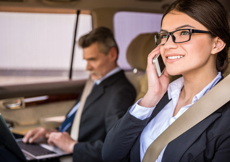 to the secretary: Young beautiful secretary in suit and glasses sitting in the car with her boss and talking on the phone.