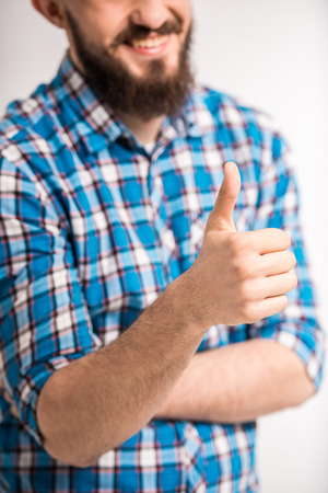 Young bearded man is showing thumb up and smiling. photo