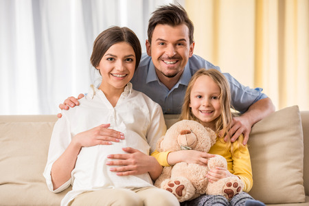 새 아기를 기다리고 행복 한 가족입니다. 그들은 카메라를보고 웃고있다. 스톡 콘텐츠