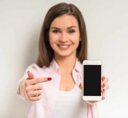 mobile phone screen: Young smiling beautiful girl showing a blank smart phone screen  on grey background.