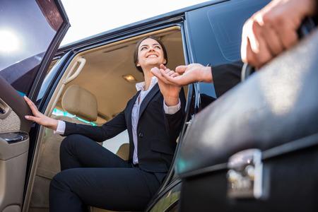 彼女の豪華な車から出てくるスーツの若い美しい笑顔の実業家。