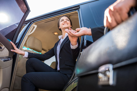 female driver: Young beautiful smiling businesswoman in suit coming out of her luxurious car. Stock Photo