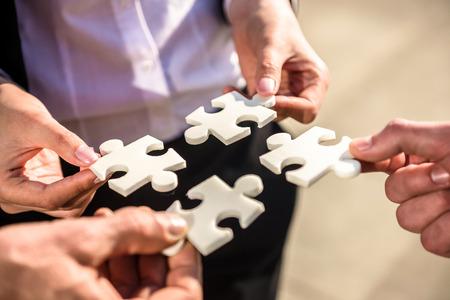 パズルの 4 つの作品を一緒にしたいビジネスの方々 のクローズ アップ。