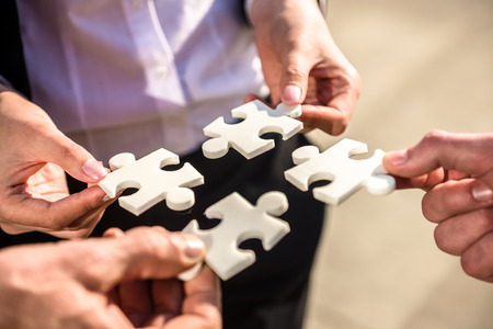 Closeup of business people wanting to put four pieces of puzzle together. Stock Photo