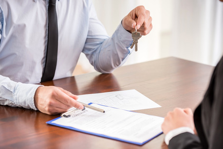 contrato de trabajo: Primer plano la mano de la mujer joven es la firma de un conract a los apartamentos.