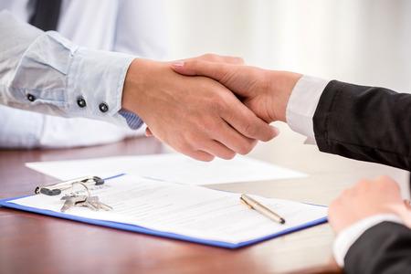agente comercial: Apretón de manos de un agente de bienes raíces y un cliente. Foto de archivo