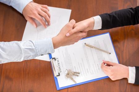agente comercial: Vista superior del apretón de manos de un agente de bienes raíces y un cliente.