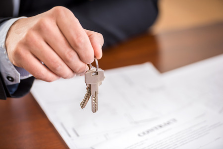 mortgages: Close-up of hand of man is holding a key from a new apartment.
