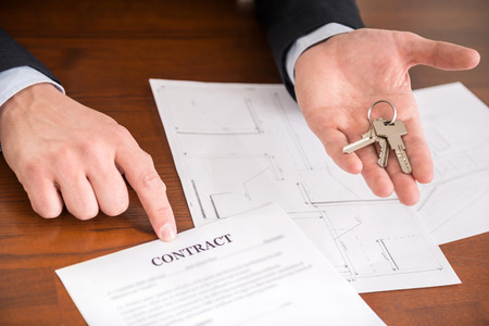 accommodation broker: Close-up of male realtor is showing a contact with key from new apartment.